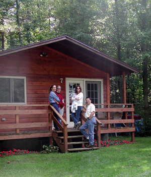 Faculty standing in front of a cabin